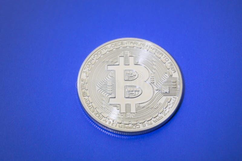 Het heldere blauwe Gouden digitale virtuele geld van Bitcoins op een blauwe achtergrond stock foto