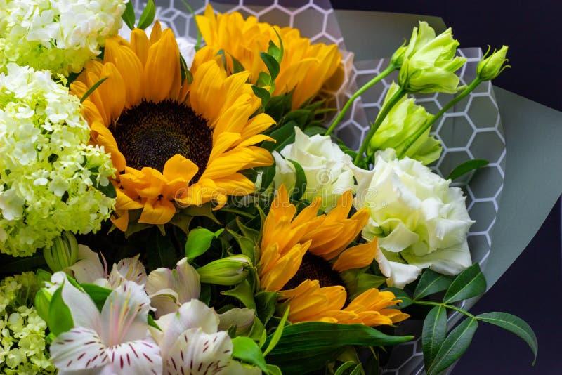 Het heldere boeket met gele zonnebloemen en nam, roze eustoma en groene viburnum bloemenachtergrond toe stock foto