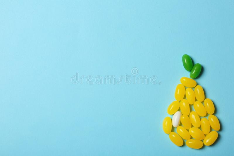 Het heldere die geleisuikergoed als peer op kleurenachtergrond wordt geschikt, vlakte lag royalty-vrije stock afbeelding