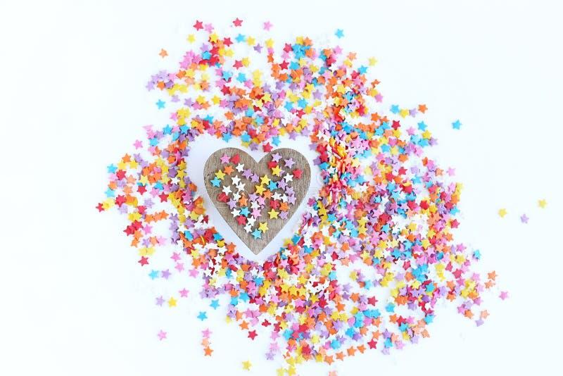 Het heldere gekleurde banketbakkerij bestrooien van sterren en houten hart op een lichte achtergrond, zachte nadruk, onduidelijk  royalty-vrije stock foto