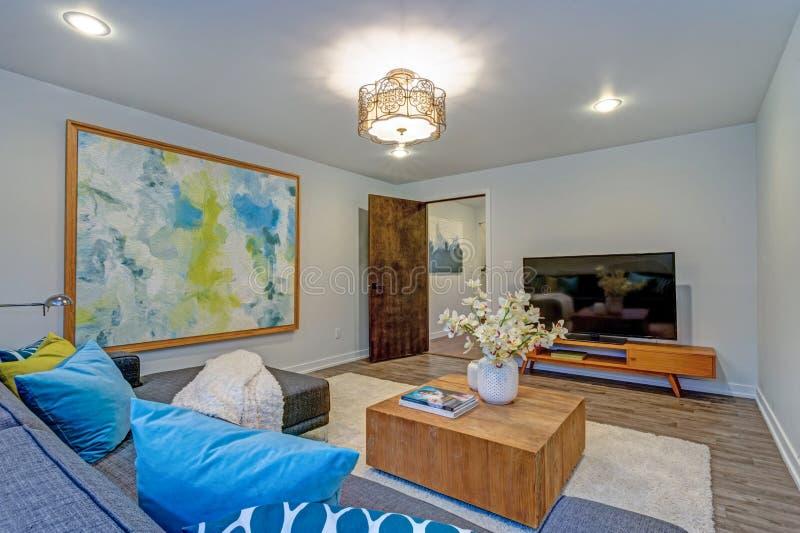 Het heldere kleurrijke moderne binnenland van de familieruimte met houten accenten royalty-vrije stock foto