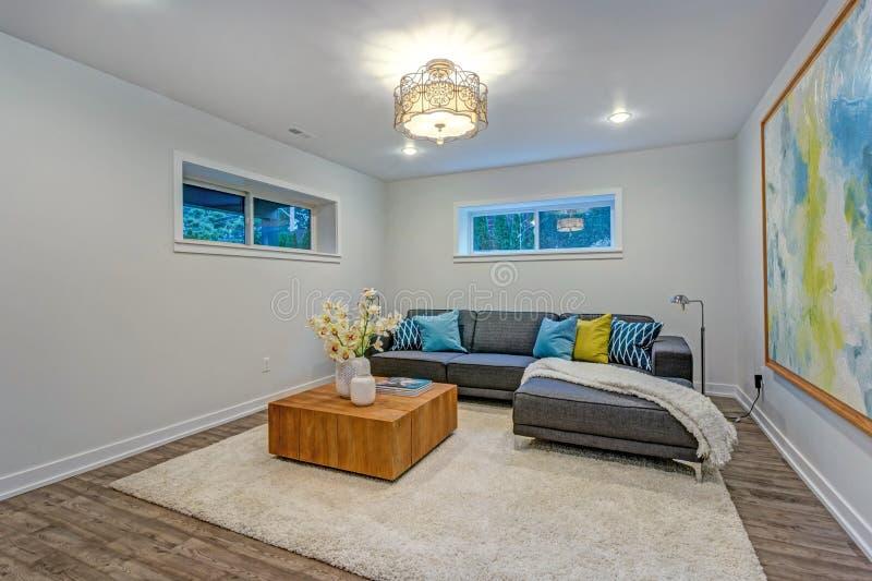 Het heldere moderne binnenland van de familieruimte met blauwe hoofdkussens op de bank stock afbeeldingen