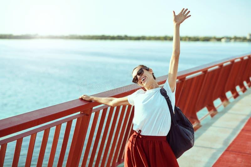 Het heldere portret die van de de zomerlevensstijl van jonge mooie vrouw in zonnebril en rode rok en witte T-shirt, op lopen royalty-vrije stock foto's