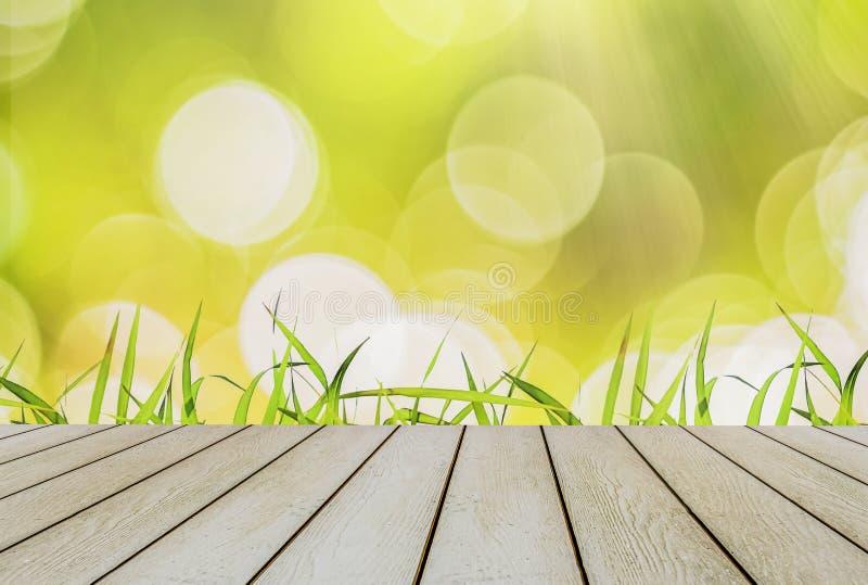 Het heldergroene gras begint met lentetijd Met gele en heldere bokeh met zonlicht en houten vloer stock foto