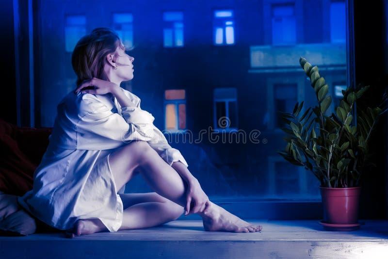 Het helft-geklede meisje in wit overhemd zit op venstervensterbank stock afbeelding