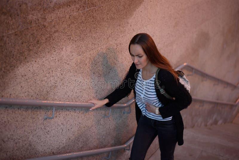 Het helft-lengte portret van de hoogste mening van een jong meisje op de treden van de metro, de overgang houdt op een zieke stom stock fotografie