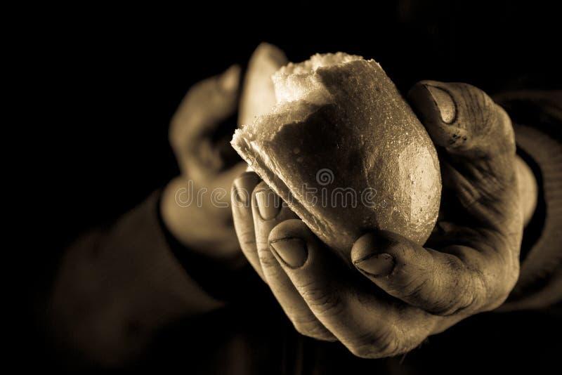 Het helpen van hand die een stuk van brood geven Slechte Mens die Brood delen, die Handconcept helpen Amber dichte omhooggaand royalty-vrije stock afbeeldingen