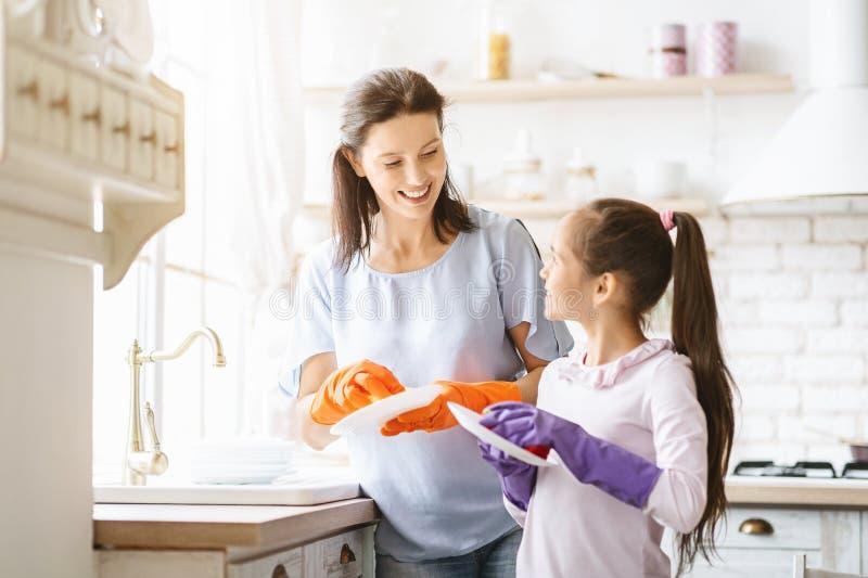 Het helpen van hand Leuke tiener die haar moeder in wasschotels helpen bij familiekeuken royalty-vrije stock fotografie