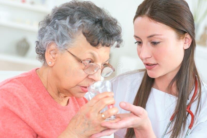 Het helpen van oude dame om medicijn te nemen royalty-vrije stock afbeeldingen