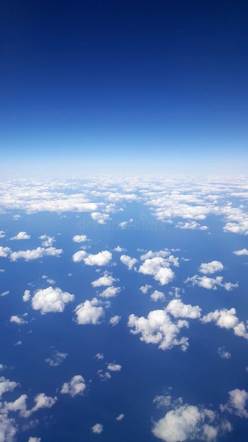 Het hemelblauw met wolken ontruimt hierboven dagmening van van het vliegtuig stock foto