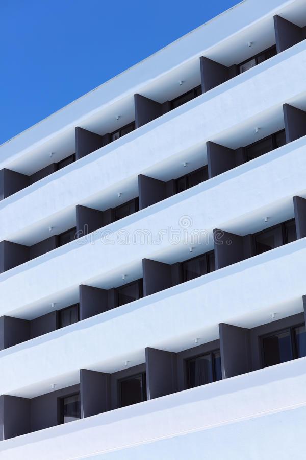 Het herhalen van patroon van vensters en balkon De voorzijde van de bouw stock afbeelding