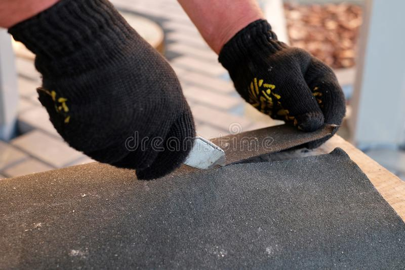 Het herstellen van dak door te snijden gevoeld voor het installeren van bitumendakspanen tijdens het waterdicht maken werkt stock afbeelding
