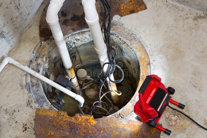Het herstellen van een zinkputpomp in een kelderverdieping stock fotografie