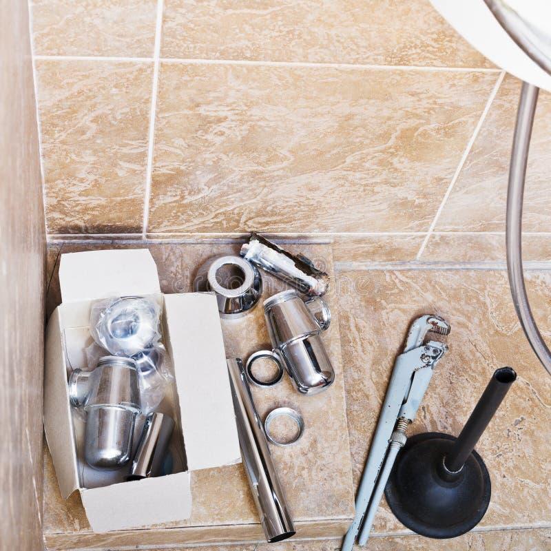 Het herstellen van geroeste gootsteensifon in badkamers stock afbeeldingen