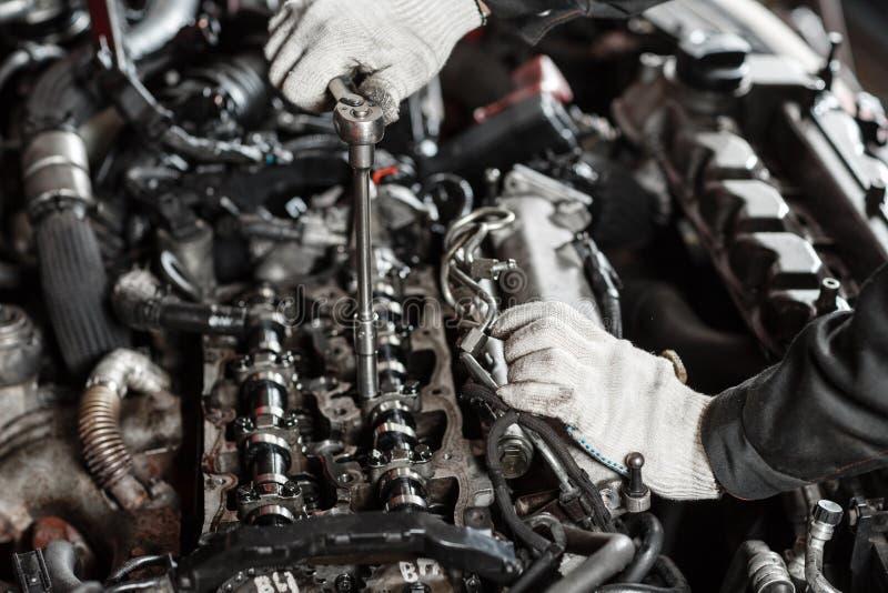 Het herstellen van moderne dieselmotor, arbeidershanden en hulpmiddel Close-up van een autowerktuigkundige die aan een automotor  stock foto's