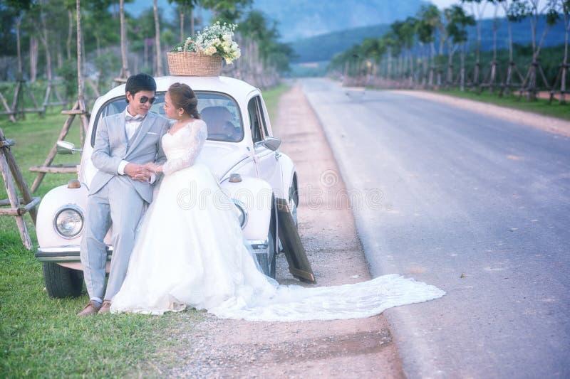Het het huwelijkspaar van Azië geniet van op de oude auto royalty-vrije stock afbeelding