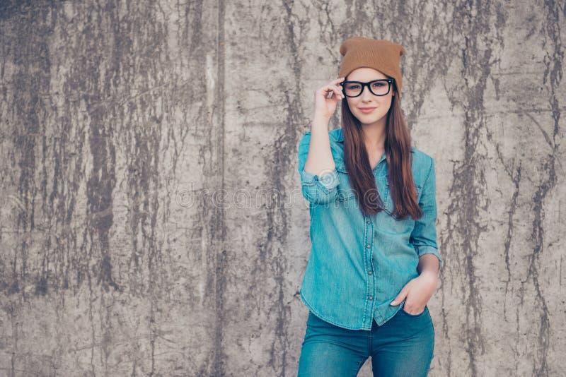 Het hete aantrekkelijke jonge meisje bevindt zich op concrete muur` s bac stock afbeeldingen
