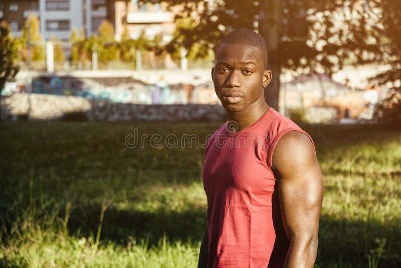 Het hete bleekgele zwarte mens stellen in stadspark royalty-vrije stock afbeelding