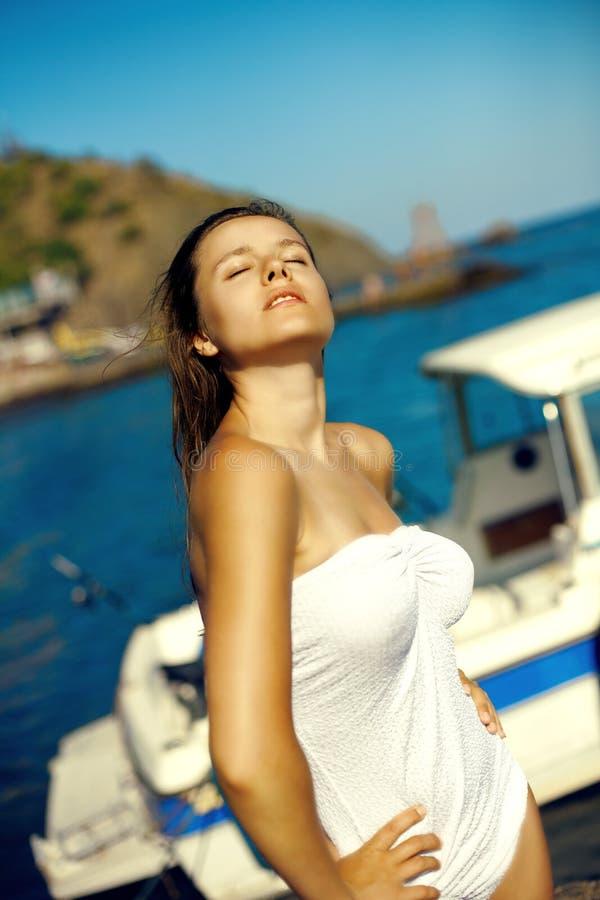 Het hete jonge mooie meisje stellen op strand in zonsondergang royalty-vrije stock foto