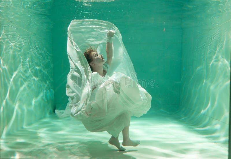 Het hete Slanke Vrouw Stellen onder water in mooie kleren alleen in diep royalty-vrije stock afbeelding