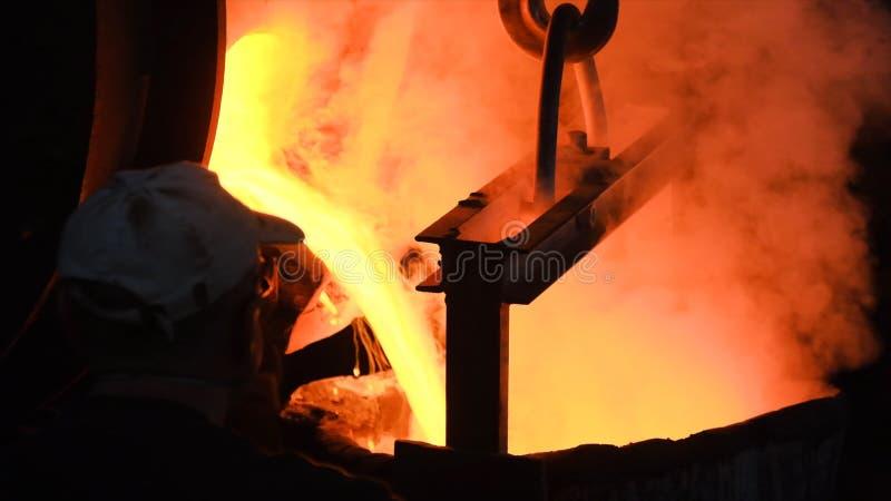Het hete staal gieten bij staalfabriek Voorraadlengte Stromend metaal bij de gieterij Het gieten van vloeibaar metaal in open haa stock afbeeldingen