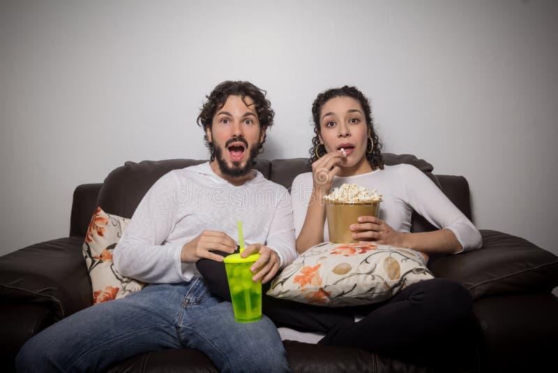 Het heteroseksuele paar eet thuis popcorn en let op film stock fotografie