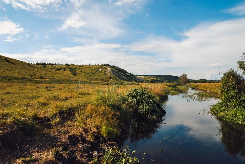 Het heuvelige landschap van het Belgorod-gebied Zonnige de lentedag die met rivier en diepe blauwe hemel in de oppervlakte nadenk stock fotografie