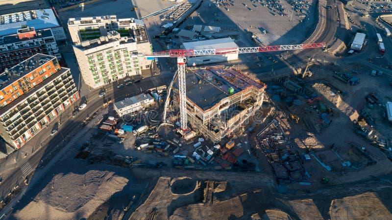 Het hijsen van kranen en nieuwe gebouwen met meerdere verdiepingen bij zonsondergang Industri?le Achtergrond Jatkasaari, Helsink royalty-vrije stock afbeeldingen