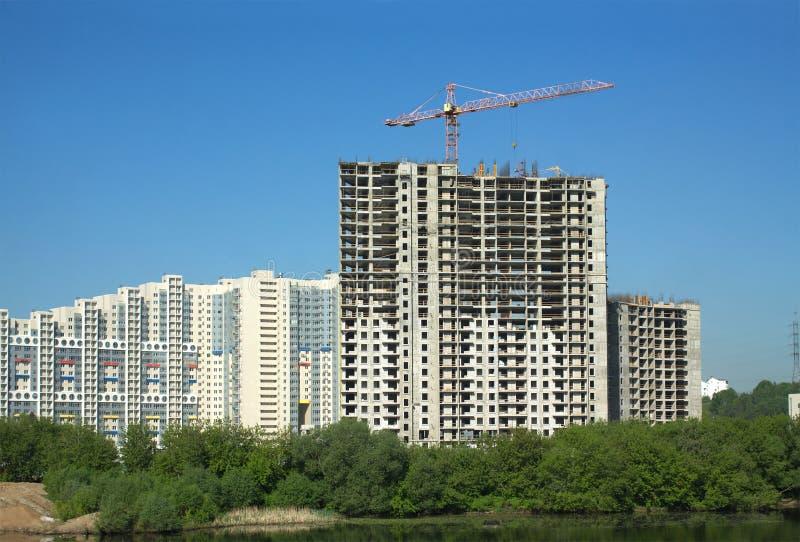 Het hijsen van torenkraan in bouw nieuwe flatgebouwen royalty-vrije stock fotografie
