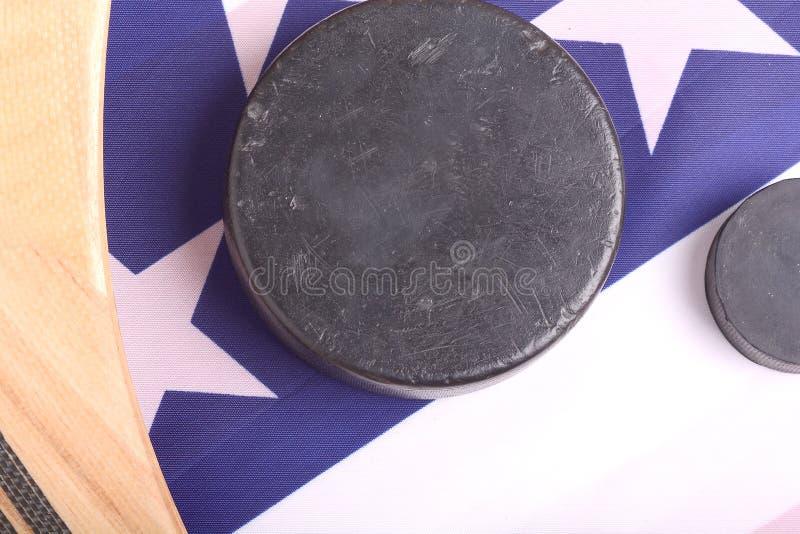 Het hockeymateriaal met inbegrip van een stok en de puck op een Amerikaan markeren om een patriottische Amerikaanse sport te conc stock foto's
