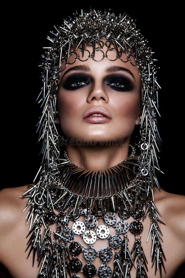Het hoge model van de manierschoonheid met metaal headwear en donkere make-up en blauwe ogen op zwarte achtergrond stock fotografie