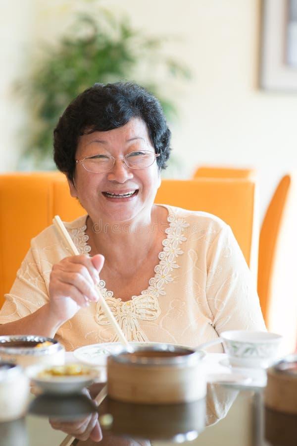 Het hogere Aziatische dineren van de Vrouw stock foto