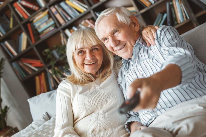 Het hogere concept die van de paar samen thuis pensionering TV-omschakelings op kanalen letten royalty-vrije stock afbeelding