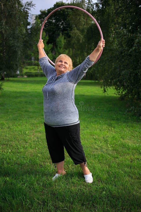 Het hogere dame doen gymnastiek- met hula-hoepel in het park stock afbeeldingen
