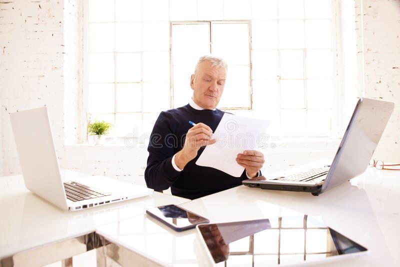 Het hogere document van de zakenmanholding in zijn hand terwijl het zitten bij bureau en het werken stock afbeeldingen