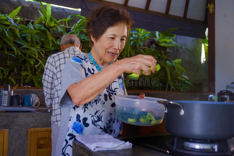 Het hogere gelukkige en mooie teruggetrokken Aziatische Japanse paar die samen thuis keuken koken die voorbereidend maaltijd onts royalty-vrije stock afbeelding