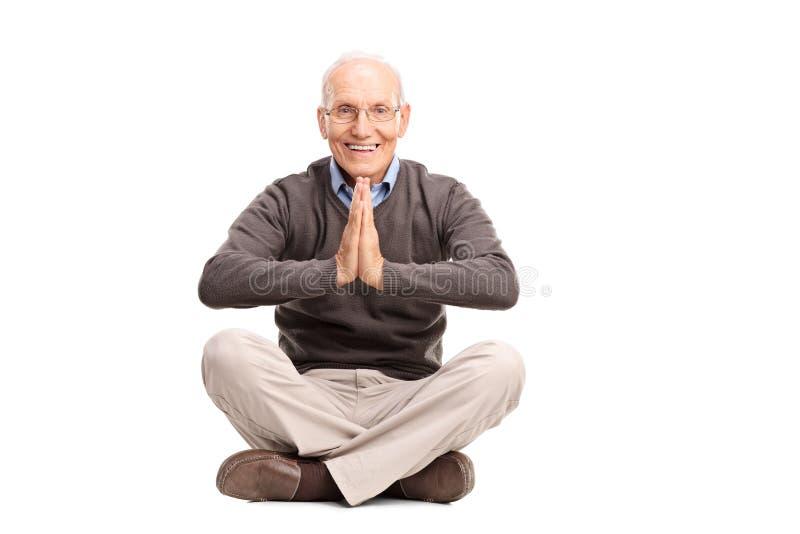 Het hogere heer mediteren gezet op de vloer stock fotografie