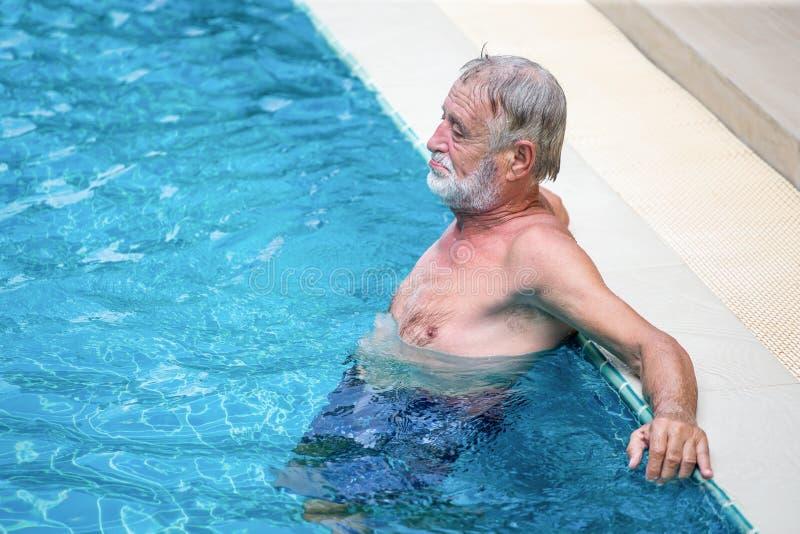 Het hogere Mens Ontspannen in Zwembad neem een onderbreking, rust, pensionering, training, fitness, sport, oefening, exemplaarrui stock foto's
