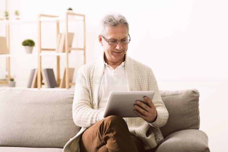 Het hogere mens surfen netto op digitale tablet thuis royalty-vrije stock afbeelding