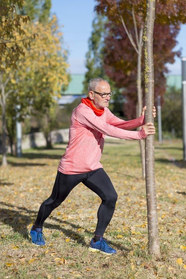 Het hogere mens uitrekken zich na jogging in het park stock afbeeldingen