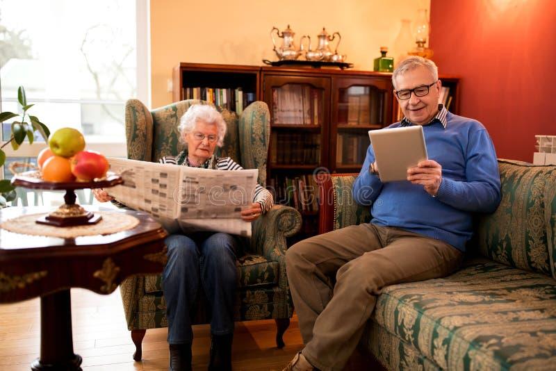 Het hogere mooie paar ontspant thuis terwijl het lezen van krant en u royalty-vrije stock afbeelding