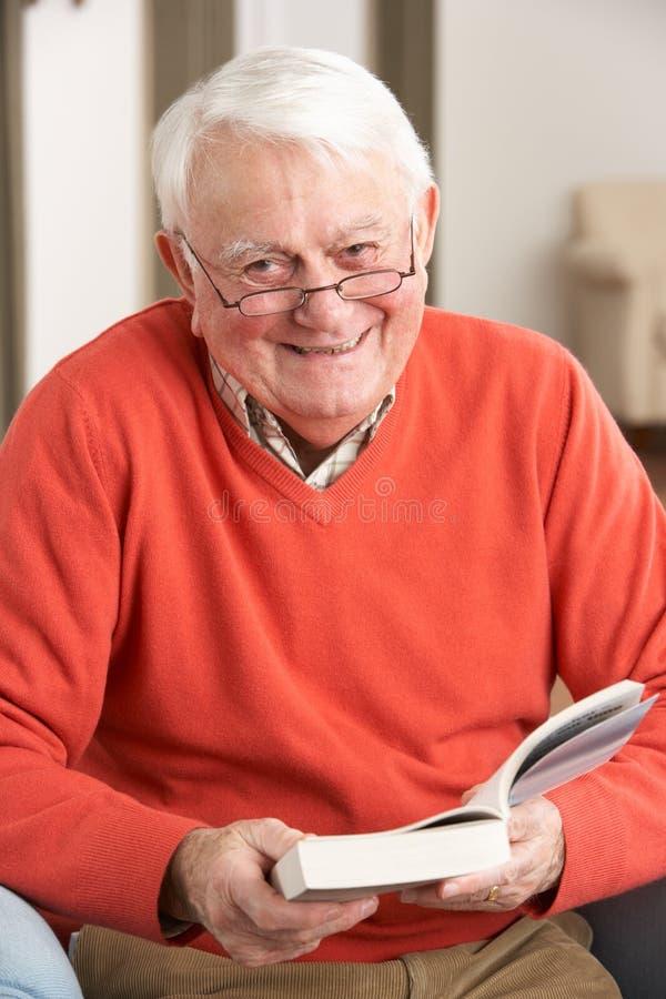 Het hogere Ontspannen van de Mens als Voorzitter die thuis Boek leest stock foto's