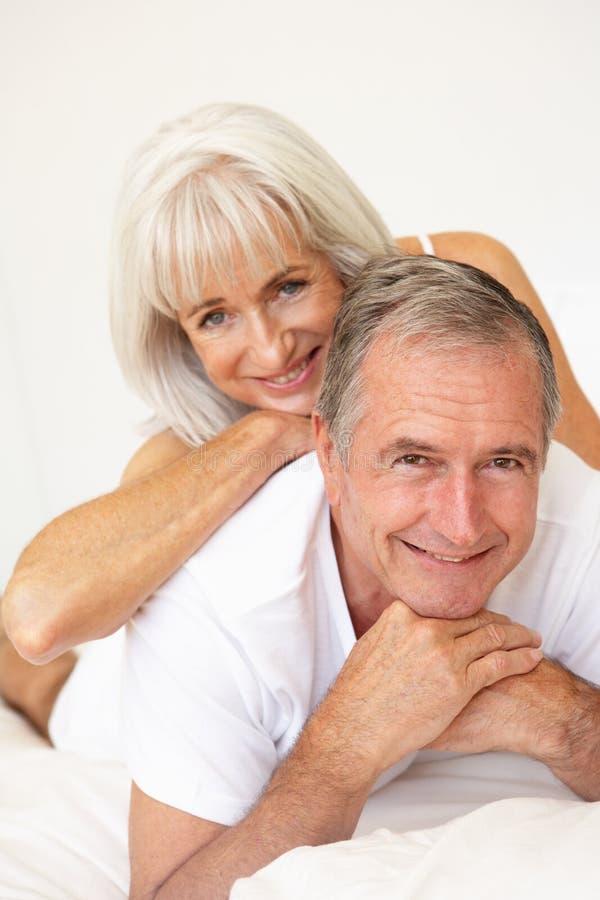 Het hogere Ontspannen van het Paar op Bed stock afbeeldingen