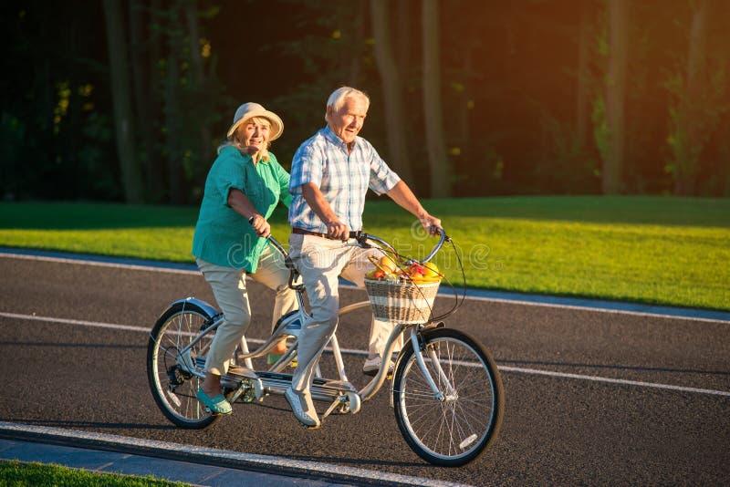 Het hogere paar berijdt fiets achter elkaar royalty-vrije stock foto's