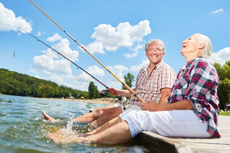 Het hogere paar bespatten met hun voeten in het water royalty-vrije stock foto's