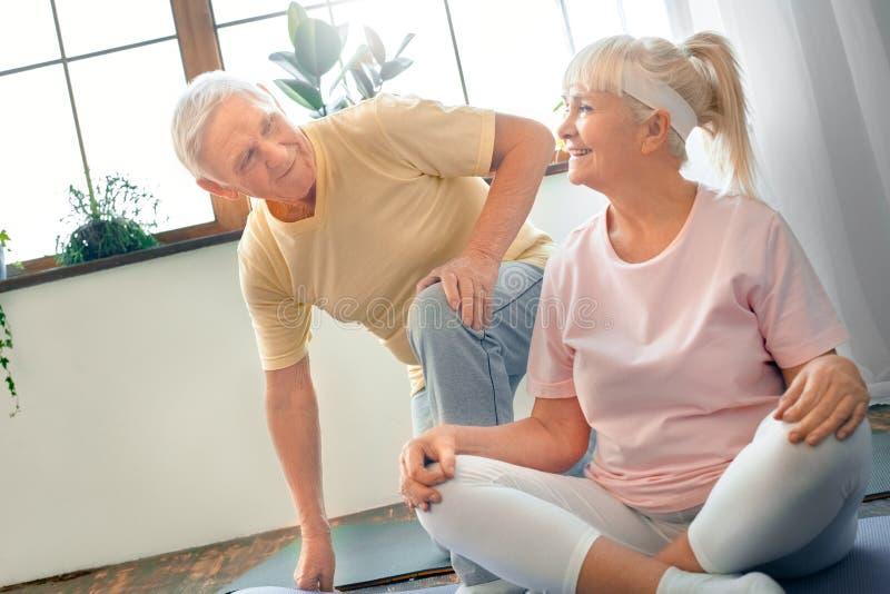 Het hogere paar die de vlinder van de yoga samen gezondheidszorg doen stelt thuis het kijken op elkaar royalty-vrije stock foto's