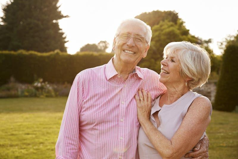 Het hogere paar die in tuin aan camera glimlachen, sluit omhoog stock foto's