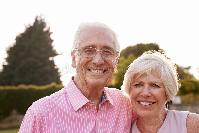 Het hogere paar die in tuin aan camera glimlachen, sluit omhoog royalty-vrije stock afbeeldingen