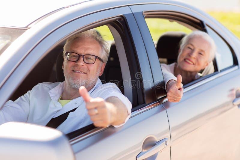 Het hogere paar drijven in auto en het tonen beduimelen omhoog royalty-vrije stock afbeeldingen