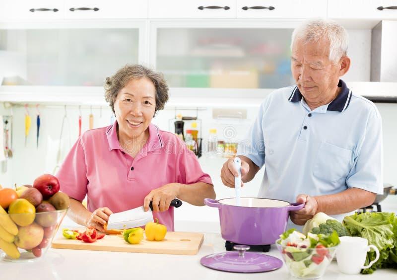 Het hogere paar koken in keuken royalty-vrije stock afbeelding